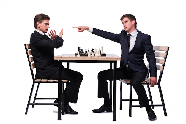 Frères jumeaux jouant aux échecs isolés sur blanc