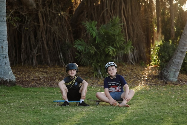 Frères mignons assis et posant sur leurs planches à roulettes en été