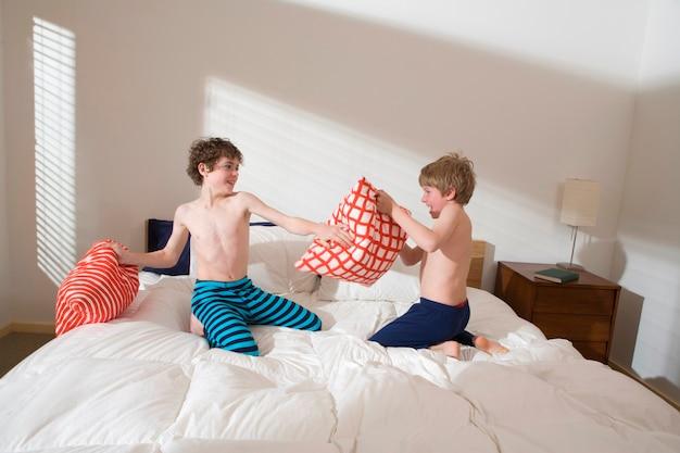 Des frères à la poitrine nue, des logements rudes et des oreillers dans un lit dans la chambre