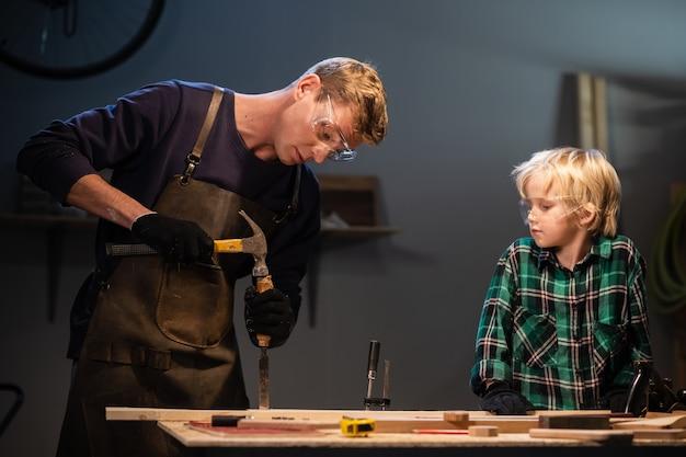 Les frères préparent un cadeau en bois pour leur mère dans le garage.