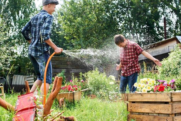 Des frères s'amusent avec de l'eau dans le village