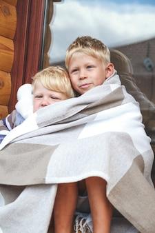 Les frères s'embrassent et s'amusent ensemble sous un plaid chaleureux et confortable.