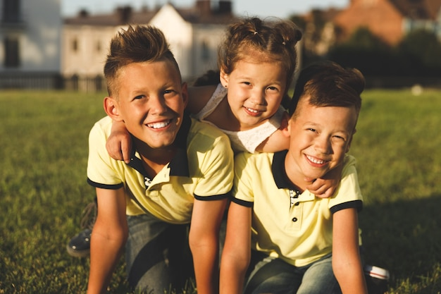 Frères avec soeur à l'extérieur en été. portraits en gros plan