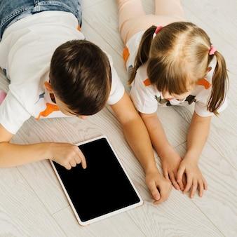 Frères et sœurs à l'aide d'une tablette numérique haute vue