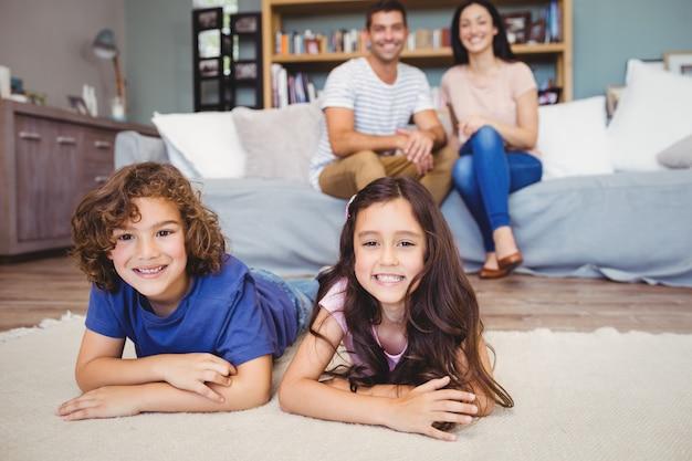 Des frères et sœurs allongés sur un tapis contre des parents assis sur un canapé
