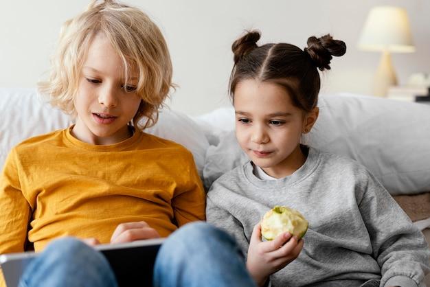 Frères et sœurs au lit jouant sur mobile et tablette