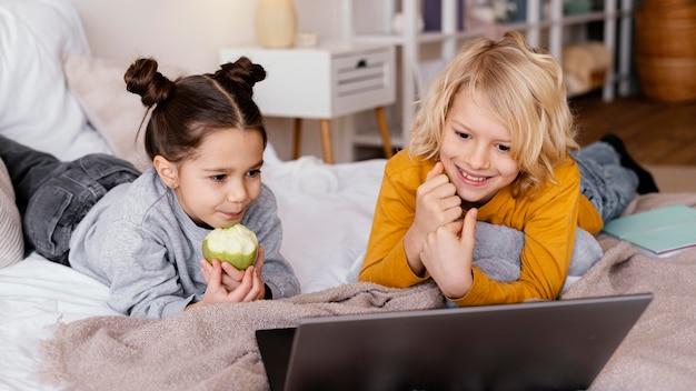 Frères et sœurs au lit, regarder une vidéo sur un ordinateur portable