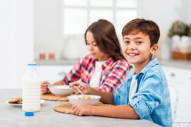 Frères et sœurs ayant leur petit-déjeuner ensemble à la maison