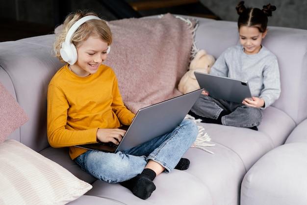 Frères et sœurs sur canapé avec ordinateur portable
