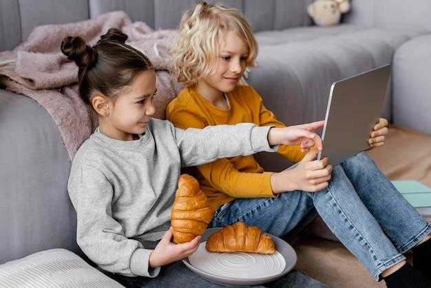 Frères et sœurs sur canapé avec tablette