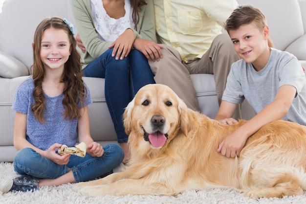 Frères et sœurs avec chien et parents assis derrière