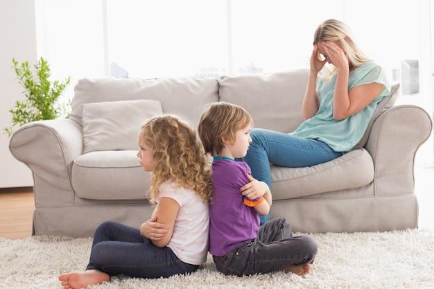 Frères et sœurs en colère assis les bras croisés avec la mère bouleversée sur le canapé