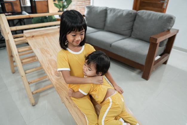 Les frères et sœurs continuent patiemment à jouer au toboggan sur le jouet triangle pikler ensemble dans le salon