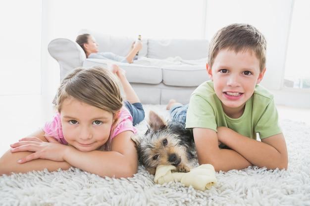 Frères et sœurs, couché sur le tapis avec yorkshire terrier, souriant à la caméra