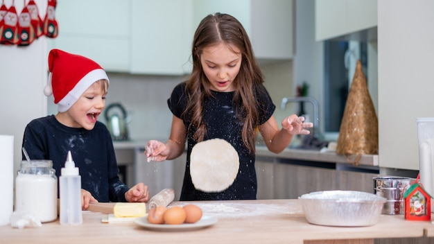 Les frères et sœurs cuisinent dans la cuisine, le garçon avec un chapeau de noël, la fille vomit la pâte. idée d'enfants heureux