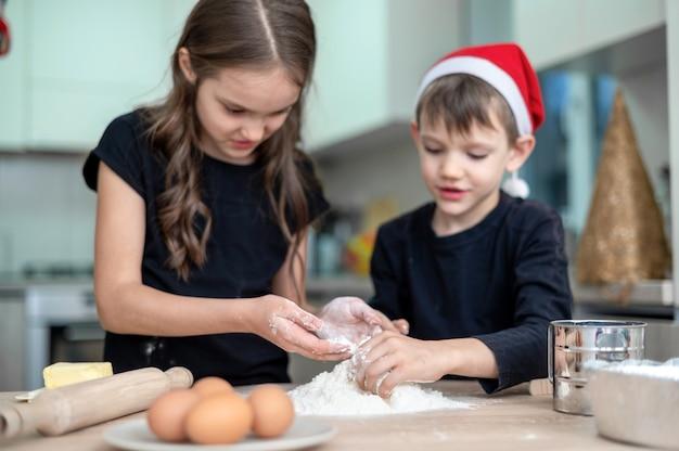 Les frères et sœurs cuisinent dans la cuisine, garçon avec un chapeau de noël. idée d'enfants heureux