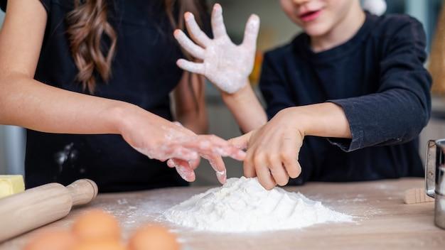 Les frères et sœurs cuisinent et s'amusent dans la cuisine. idée d'enfants heureux