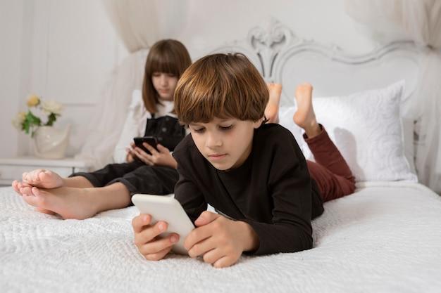Frères et sœurs dans la chambre avec téléphone