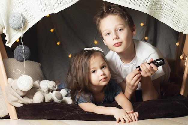 Frères et sœurs dans une hutte de chaises et de couvertures