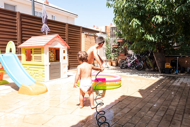 Des frères et sœurs heureux jouent avec des tuyaux d'eau dans la cour.