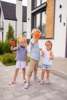 Frères et sœurs heureux joyeux debout devant leur maison