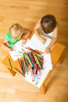 Frères et sœurs jouant avec des crayons