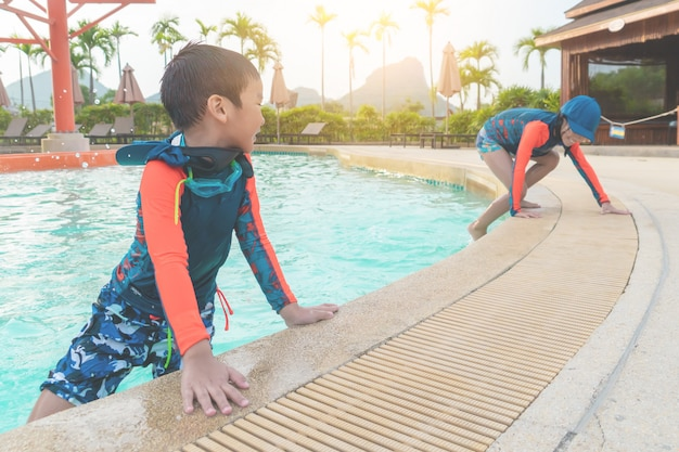 Frères et sœurs en jouant ensemble dans la piscine du parc aquatique aqua.