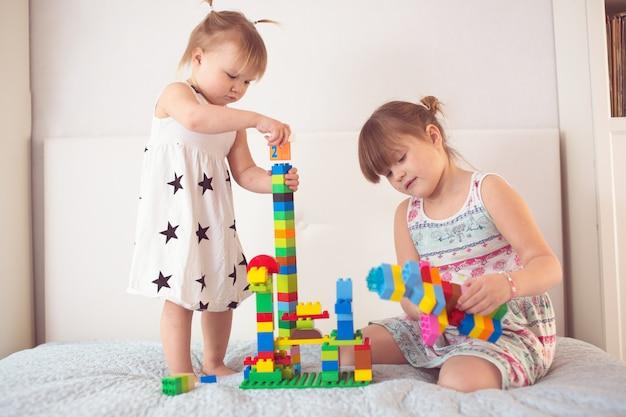Frères et sœurs jouent avec le constructeur dans un véritable intérieur