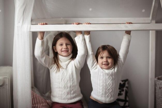 Les frères et sœurs jouent dans la chambre des enfants, véritable intérieur