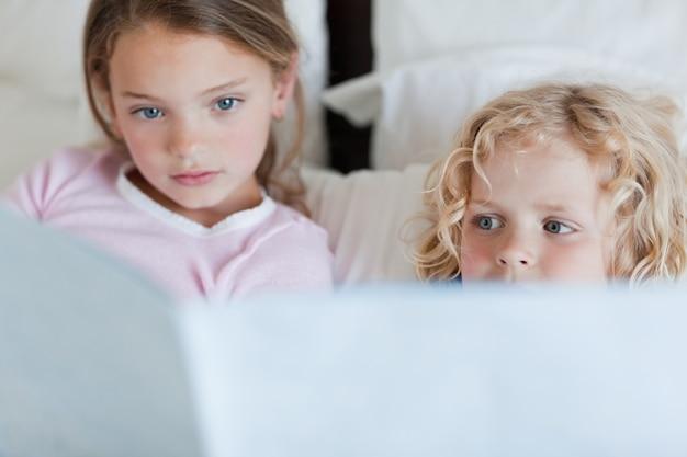 Frères et sœurs lisant une histoire au coucher