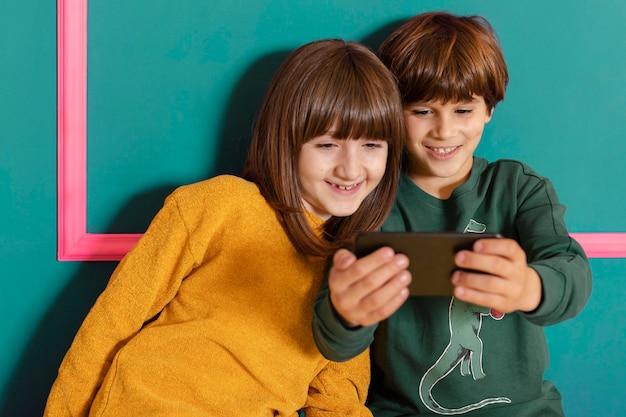 Frères et sœurs à la maison avec mobile