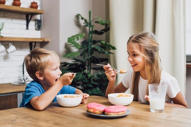 Frères et sœurs mangeant ensemble dans la cuisine