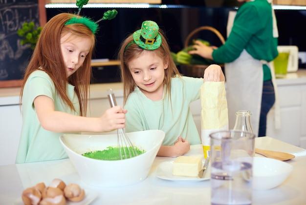 Frères et sœurs mélangeant le glaçage fondant vert
