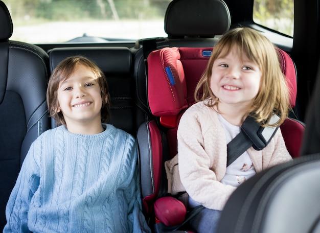 Frères et sœurs mignons sur la banquette arrière en voiture