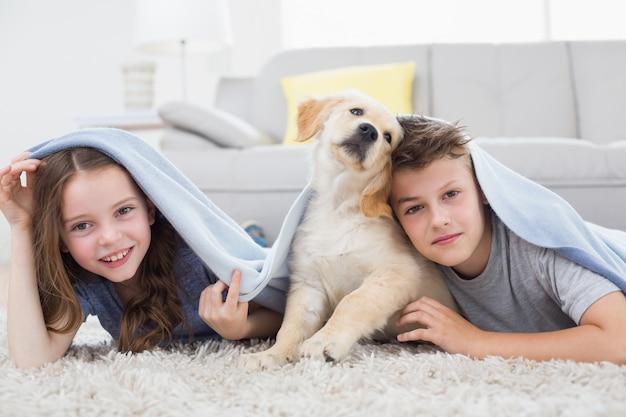 Frères et sœurs mignons avec chien sous couverture dans le salon