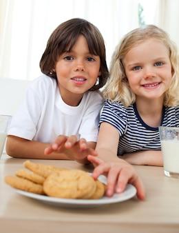 Frères et sœurs mignons mangeant des biscuits