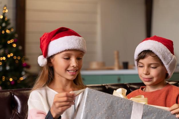 Frères et sœurs ouvrant un cadeau de noël ensemble