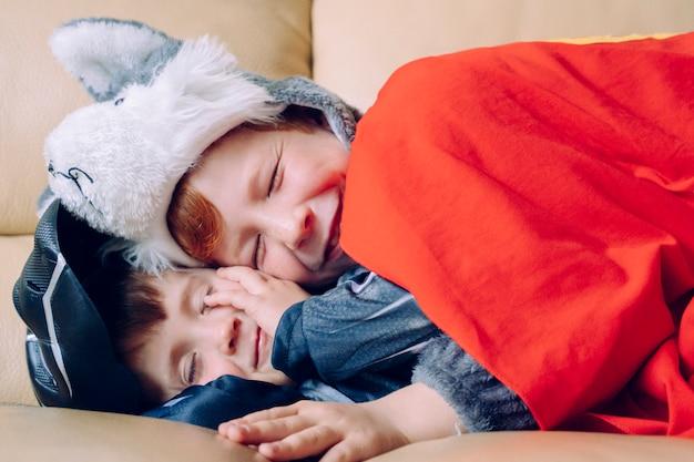 Les frères et sœurs partagent un moment d'amour à la maison. deux frères dormant et s'amusant sur le canapé blanc rêvant avec des super héros. concept de convivialité familiale.