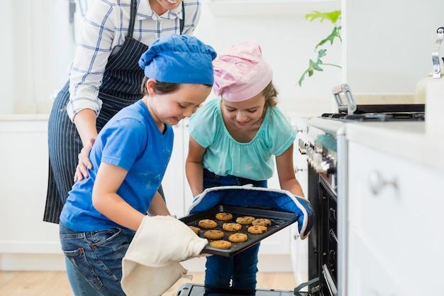 Frères et sœurs plaçant le plateau de biscuits dans le four