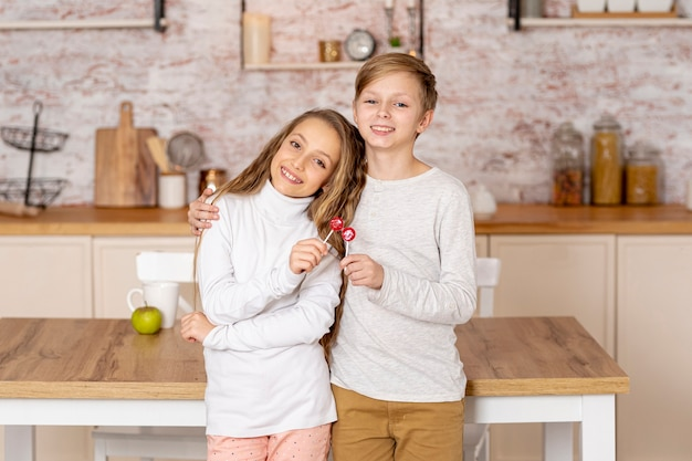 Frères et sœurs posant ensemble dans la cuisine