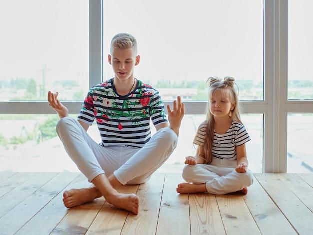 Frères et sœurs de race blanche frère et sœur faisant du yoga à la maison par la fenêtre parents de la famille