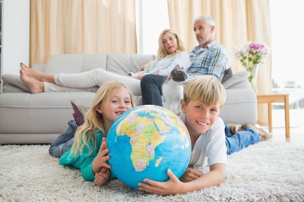 Frères et sœurs regardant le globe sur le sol