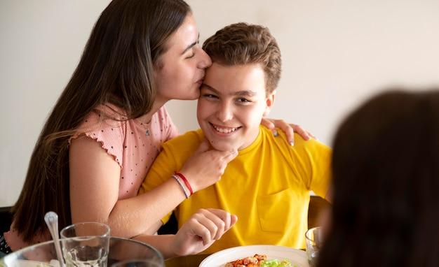 Frères et sœurs s'embrassant au déjeuner en famille