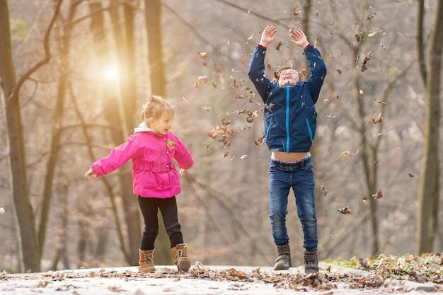 Frères et sœurs sautant ensemble dans une forêt avec des feuilles sèches en hiver