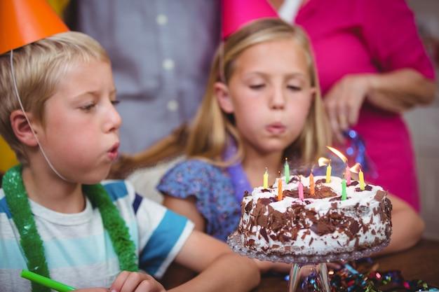 Frères et sœurs soufflant des bougies d'anniversaire