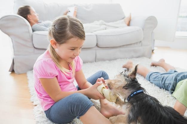 Frères et sœurs sur le tapis avec leur yorkshire terrier