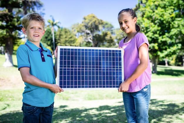 Frères et sœurs tenant un panneau solaire
