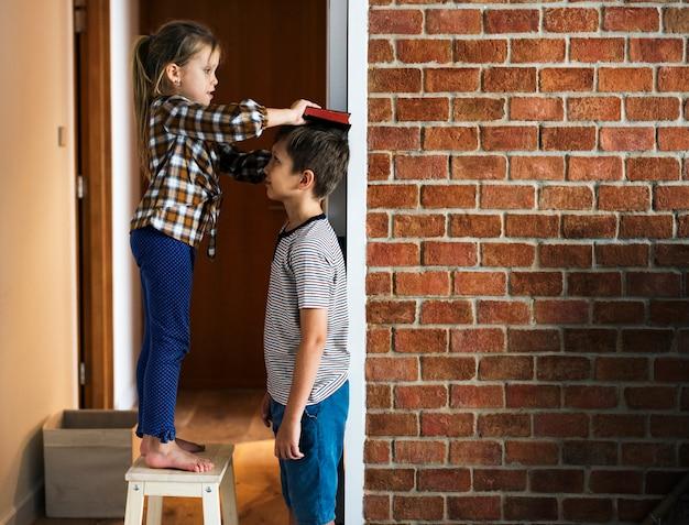 Frères et soeurs vérifiant la hauteur