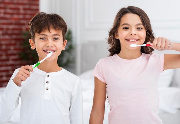 Frères et soeurs de la vue de face brosser les dents ensemble