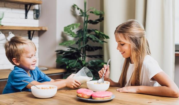 Frères et soeurs vue de face manger ensemble dans la cuisine